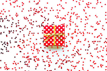 Valentine's Day concept - a gift box over scattered heart shaped confetti background.