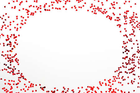 Valentine's Day background - a frame of scattered heart shaped confetti over white background. Zdjęcie Seryjne