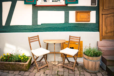 Cosy wooden table and chairs set in front of a typica german old style house. Zdjęcie Seryjne