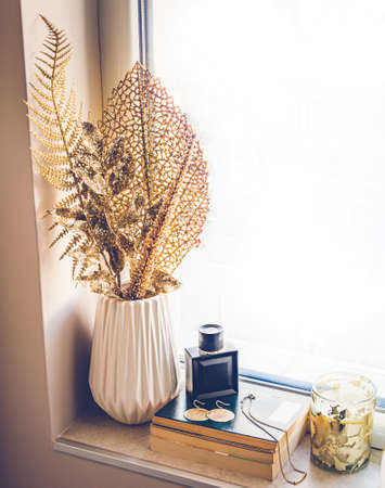 Feminine perfume and gold jewellery laid over a stack of books on the window sill. Home decor in golden color