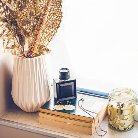 Feminine perfume and gold jewellery laid over a stack of books on the window sill. Home decor in golden color Zdjęcie Seryjne - 140552097