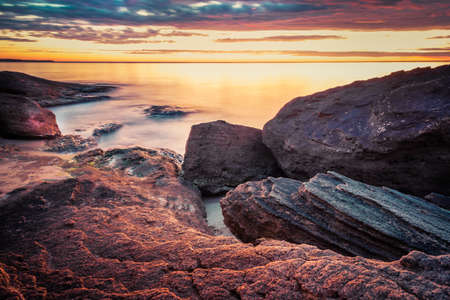 Picturesque sunrise over a rocky beach. Zdjęcie Seryjne - 139488317