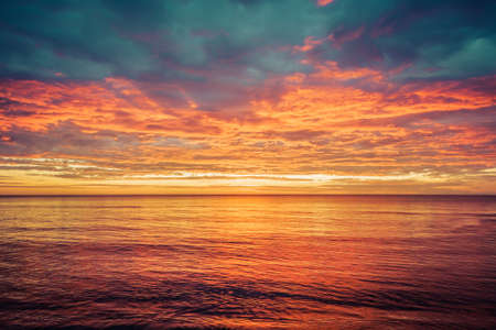 Picturesque sunrise over the sea. Dramatic sky colored in orange and red. Zdjęcie Seryjne - 139488768