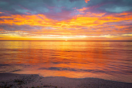Picturesque sunrise over the sea. Dramatic sky colored in orange and red. Zdjęcie Seryjne