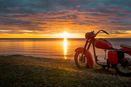 A skeleton of an old red motorcycle against the picturesque sunrise.