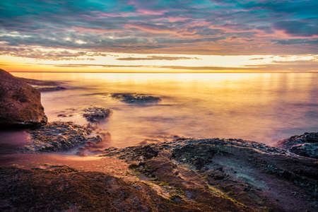 Picturesque sunrise over a rocky beach.
