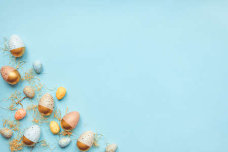 Top view of easter eggs colored with golden paint and differen colors. Blue background. Copy space.