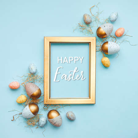Top view of easter eggs colored with in differen colors arranged around a golden photo frame. Blue background. Happy Easter text.