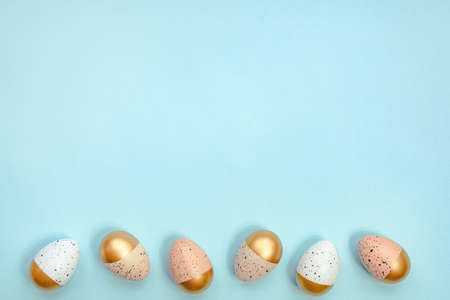 Top view of easter eggs colored with golden paint and different colors. Blue background. Copy space. Zdjęcie Seryjne