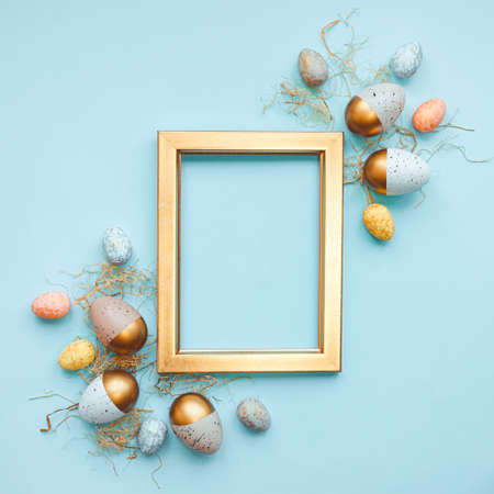 Top view of easter eggs colored with in differen colors arranged around a golden photo frame. Blue background. Copy space. Zdjęcie Seryjne - 143372755