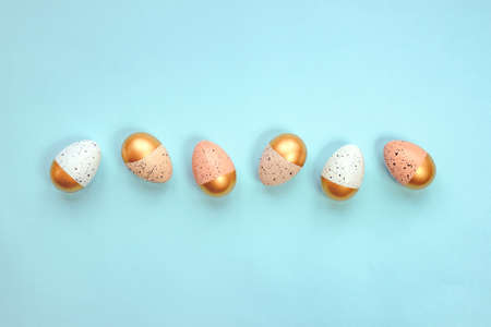 Top view of easter eggs colored with golden paint and different colors. Blue background. Copy space. 写真素材