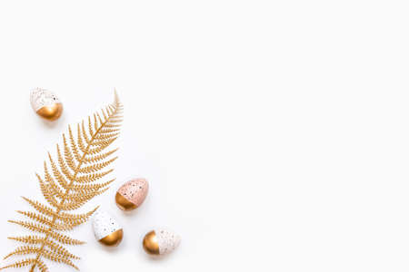Top view of golden palm leaf and easter eggs colored with golden paint. Various clorful designs. White background. Zdjęcie Seryjne - 143677974