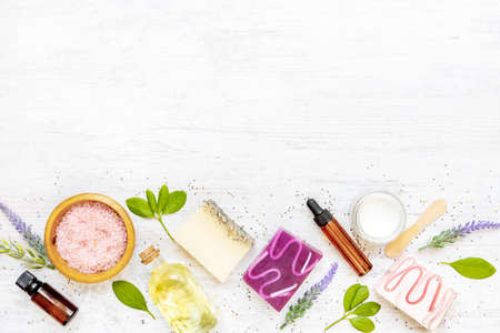 Top view of organic soaps and cosmetics arranged with lavender, herbs, chia seeds and essential oils. White rusric background, copy space.