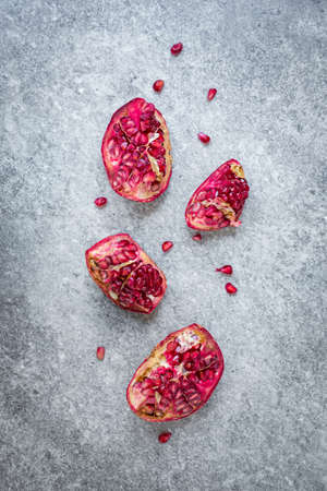 Top view of ripped pomegranate fruit over grey stone background. Zdjęcie Seryjne - 144352035