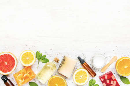 Top view of handmade organic soaps and cosmetics arranged with citrus fruits, herbs, chia seeds and essential oils. White rusric background, copy space.