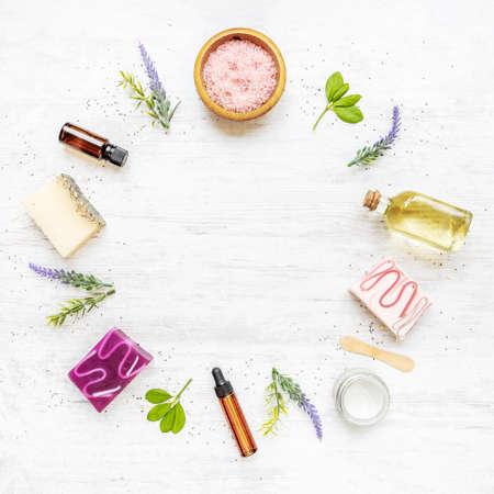 Top view of organic soaps and cosmetics arranged in circle with lavender, herbs, chia seeds and essential oils. White rusric background, copy space.