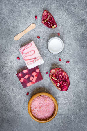 Top view of organic pomegranate fruit soaps and cosmetics over grey stone background.