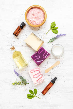 Top view of organic soaps and cosmetics arranged with lavender, herbs, chia seeds and essential oils. White rusric background.