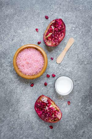 Top view of organic pomegranate fruit cosmetics over grey stone background. Zdjęcie Seryjne - 143406869