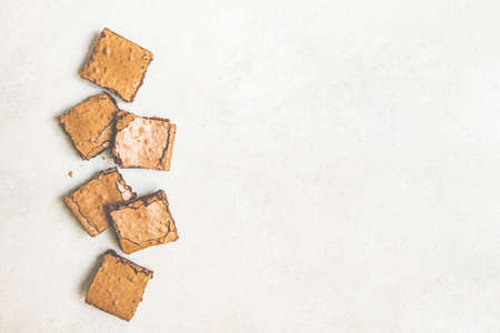 Top view of freshly baked home made brownie cake cut in squares over white rustic background. Copy space. Zdjęcie Seryjne