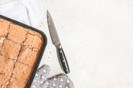 Top view of freshly baked home made brownie cake cut in squares over white rustic background. Copy space. 写真素材