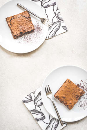 Top view of two dessert plates with brownie cake over white rustic background. Zdjęcie Seryjne