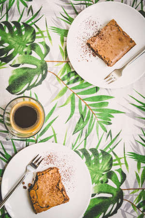Top view of a cup of coffee and two dessert plates with brownie cake over table-cloth with green leaves pattern.