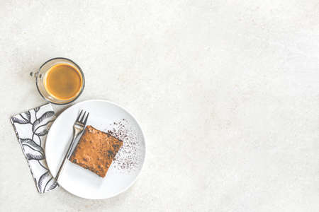 Top view of a cup of coffee and a dessert plate with brownie cake over white rustic background. Zdjęcie Seryjne - 146752471