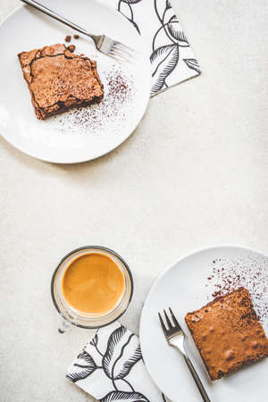 Top view of a cup of coffee and two dessert plates with brownie cake over white rustic background.
