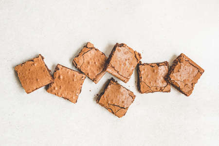 Top view of freshly baked home made brownie cake cut in squares over white rustic background. Zdjęcie Seryjne