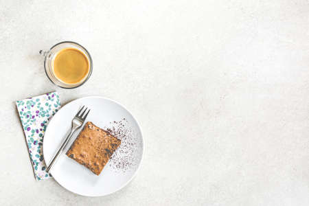 Top view of a cup of coffee and a dessert plate with brownie cake over white rustic background. 写真素材