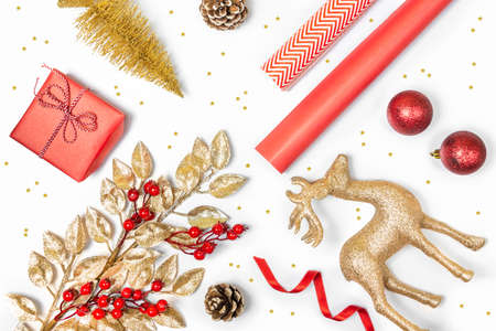 Christmas presents preparation - gift box, mistletoe, fircones,reindeer, christmas balls and paper in golden and red colors over white background.