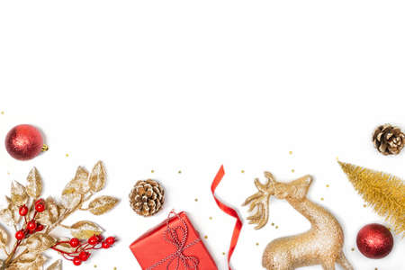 Christmas background - gift box, mistletoe, fircones,reindeer and christmas balls in golden and red colors over white background. Copy space, flat lay.