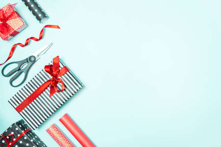 Gift boxes wrapped in black and white striped, dotted and red paper with wrapping materials over a blue background. Various designes wrapped presents preparation. Copy space.