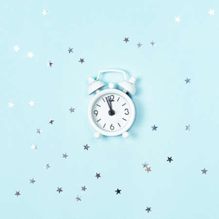 White vintage style alarm clock showing five minutes left untill midnight over blue background with silver stars sequins. New Year advent. 写真素材