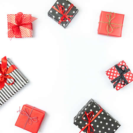 Top view of gift boxes wrapped in black and white striped, dotted and red paper over a white background. Various designes wrapped presents. Copy space