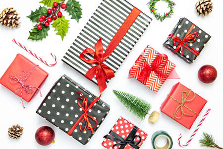 Top view od arranged gift boxes wrapped in striped and dotted black and white and red paper over white background. Christmas presents and ornament preparation.