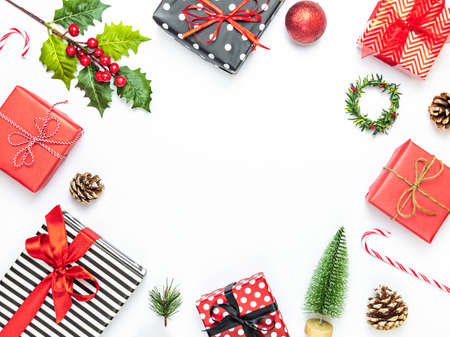 Gift boxes wrapped in striped and dotted black and white and red paper over white background. Christmas presents and ornament preparation. Copy space.