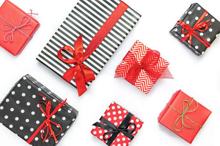 Top view of gift boxes wrapped in black and white striped, dotted and red paper over a white background. Various designes wrapped presents.
