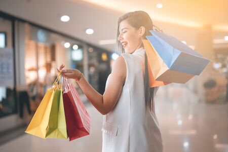 Beautiful smile girl holding colorful shopping bag and credit card Banco de Imagens