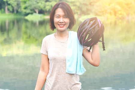 Asian Sport Woman with Cycling Helmet Acting near the Lagoon