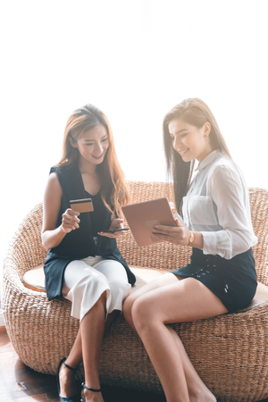 Two Business Woman Shopping Online by Smartphone or Tablet Pay by Cradit Card Banco de Imagens