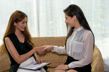 Two Asian Business Woman Talking, Dealing and Signing Contract Banco de Imagens