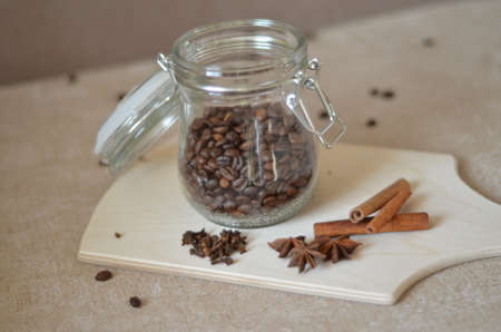Coffee bean in glass bottle. Glass jar with coffee beans on a cutting board three cinnamon sticks anise cloves Stock Photo