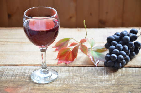 Brush black grapes on the wooden surface, copy space. red wine and grapes. Wine and grapes in vintage setting with corks on wooden table. with red leaves. autumn concept