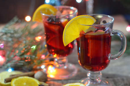 christmas hot mulled wine with cinnamon cardamom and anise on wooden background.