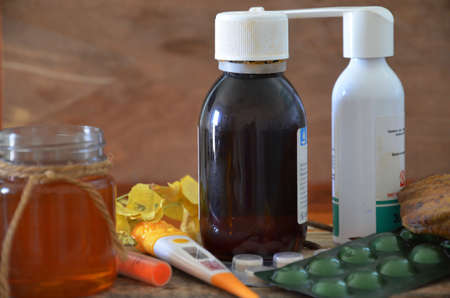 Different drugs on wooden background.Alternative remedies and traditional pills to treat colds and flu. Natural medicine and conventional medicine concept.
