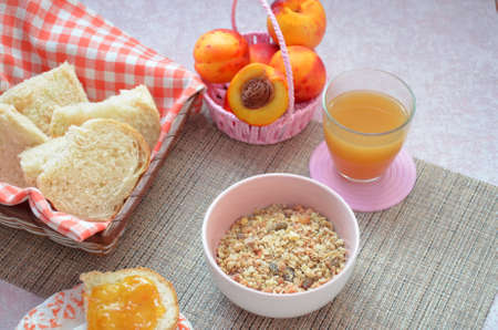 Healthy breakfast ingredients. Bowl of oat granola. beautiful fresh tasty Breakfast on the table. white bread toast basket sliced. sandwich with jam. peach juice. fresh fruit peaches.