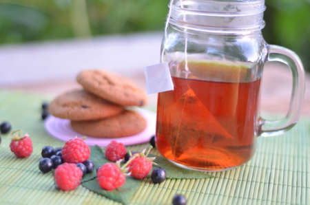 Cup of vitaminic tea with cookies and berries on table close-up Stock Photo