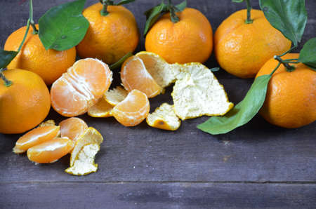 Tangerines oranges, mandarins, clementines, citrus fruits with leaves on the rustic wooden background, copy space. winter. Stock Photo